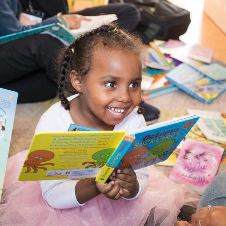 Little girl holding a book and smiling