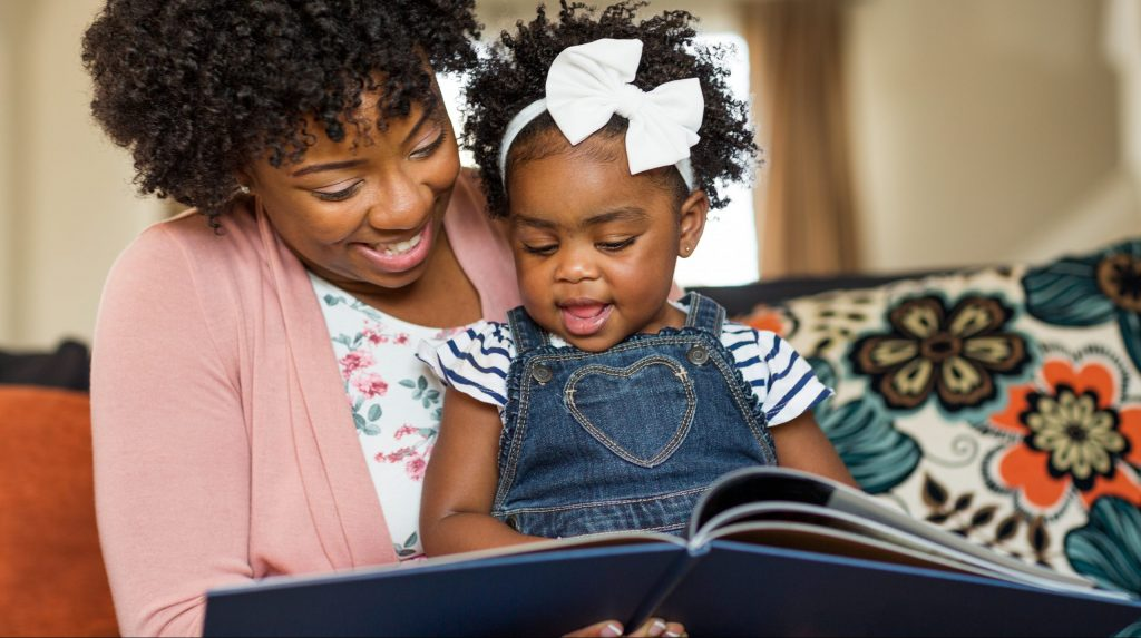 Mother reading a book to her little girl