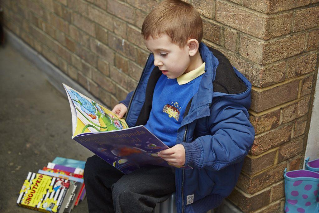 Child reading on doorstep