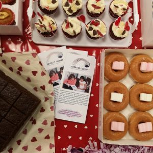 Lots of cakes and cupcakes on a table for a bake sale